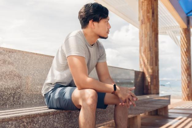 空気を冷やす海のそばの小屋に座っている孤独な男。