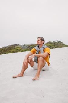 海の海の天気の休暇のビーチを楽しんでいるビーチの最前線の砂丘に座っている孤独な男
