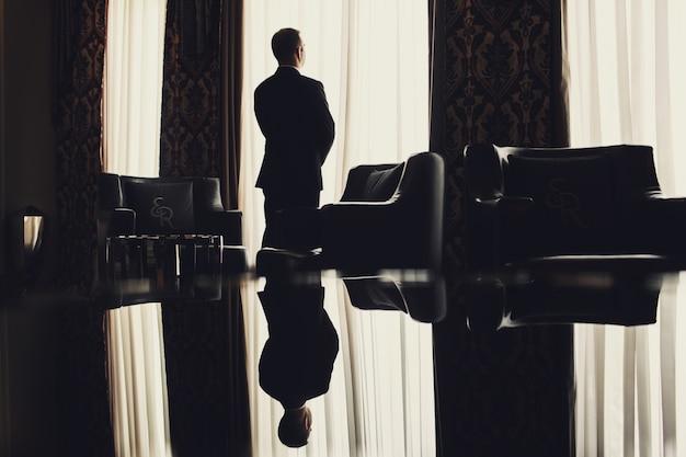 Одинокий мужчина стоит перед окном в комнате