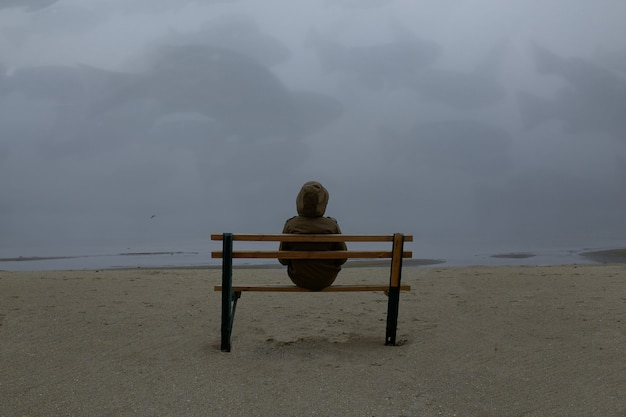 霧のビーチの上を歩く孤独な男