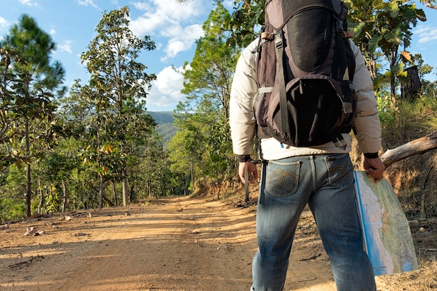 Lonely man wearing jeans and leather boots walking along the path strewn with rocks.