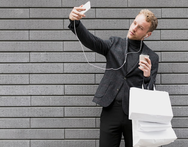 Lonely man with earphones taking a selfie