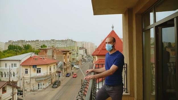 コロナウイルス隔離中にテラスでマスクを持つ孤独な男。
