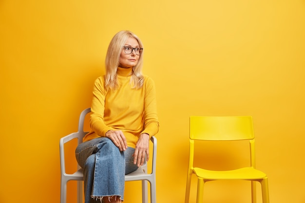 Одинокая женщина средних лет сидит возле пустого стула, нуждается в общении, задумчиво смотрит в сторону, одетая в повседневную водолазку и джинсы