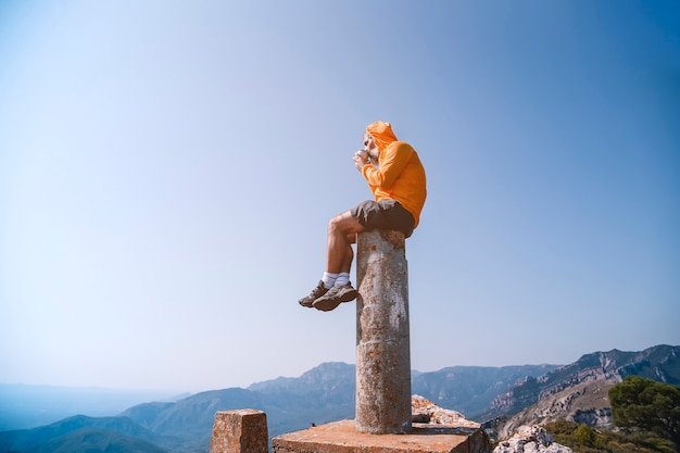 Lonely moment. the man sits on top of the rock and watches the valley having a coffee