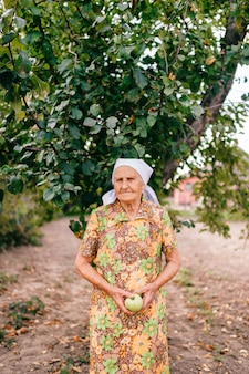 Lonely old woman with green apple in hands standing in garden in front of apple tree.  unhappy sad female with wrinkled skin portrait. 90 years old lady