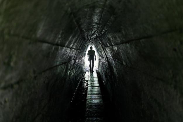 Одинокий прохожий в темном туннеле. свет в конце туннеля.