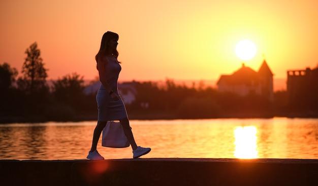 따뜻한 저녁에 호숫가를 혼자 걷고 있는 외로운 보행자 여성. 고독과 휴식 개념입니다.