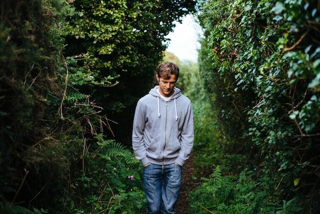아름다운 녹지와 함께 길을 따라 걷는 외로운 사람