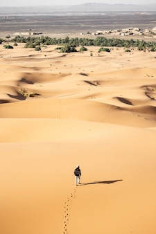 Persona sola che cammina in un deserto vicino alle dune di sabbia in una giornata di sole