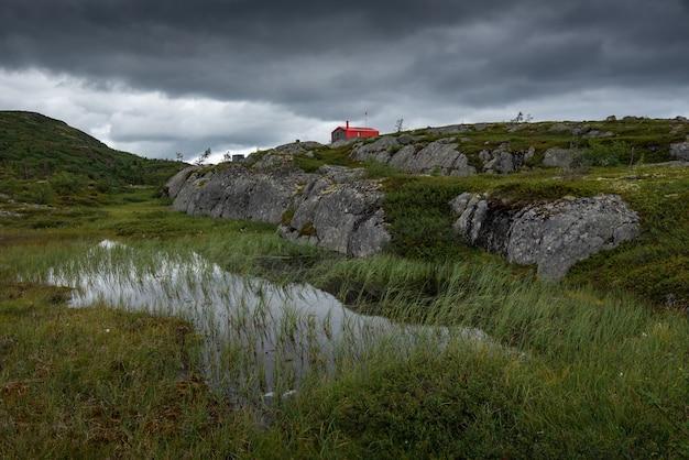 Одинокий красный дом (дублей) среди тундры и камней. северная природа кольского полуострова