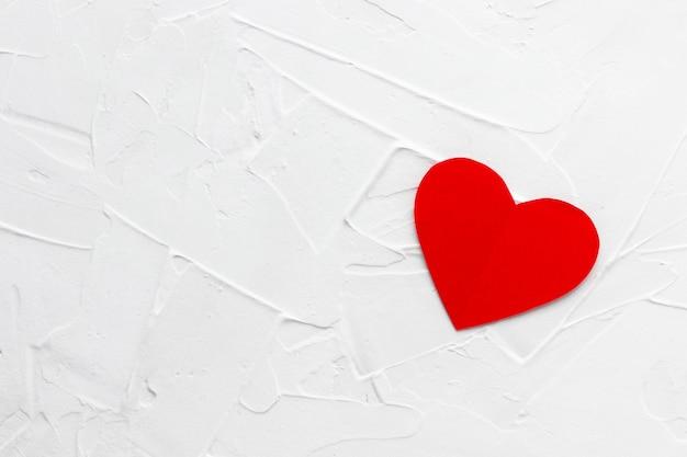 白いパテテクスチャ背景に孤独な赤いパパーハート。バレンタインデーのコンセプト。
