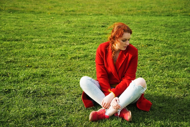 Lonely redhaired woman in a red coat and light jeans sits on green grass in the park during the day