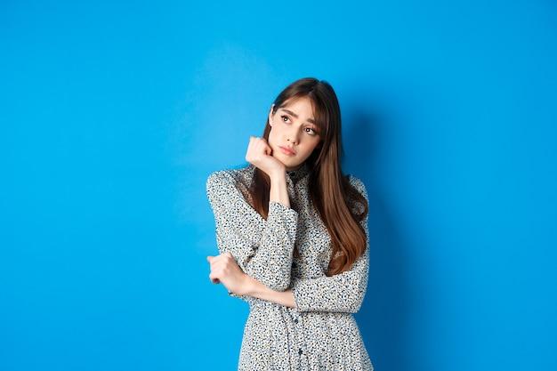 외로운 로맨틱 소녀 드레스, 슬프고 우울한 얼굴로 로고를보고 파란색에 서.