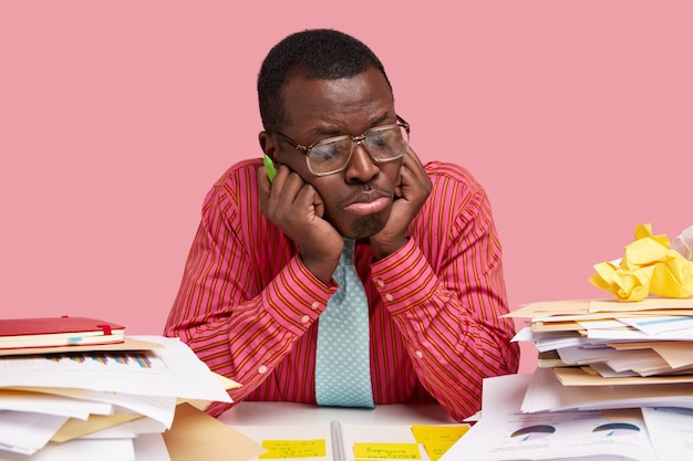 Lonely sad dark skinned office worker keeps hands under chin, focused down, looks at business papers in displeasure, wears pink shirt, holds pen