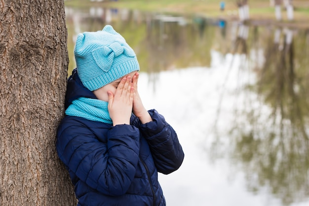 A lonely sad girl stands covering her face with the hands of a tree on the shore of the lake. mental health. teenage years