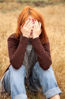 Одинокая грустная рыжая девушка на поле