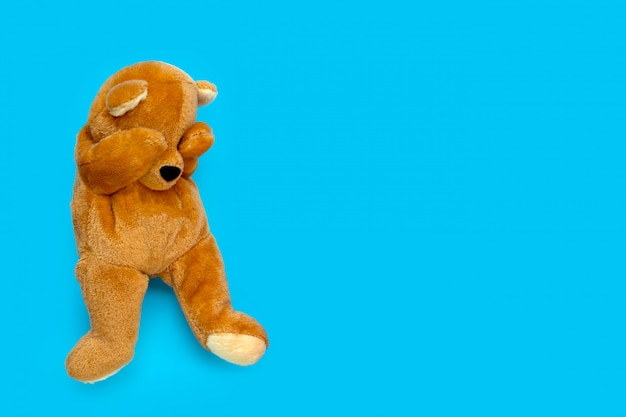 Lonely sad teddy bear on blue background.
