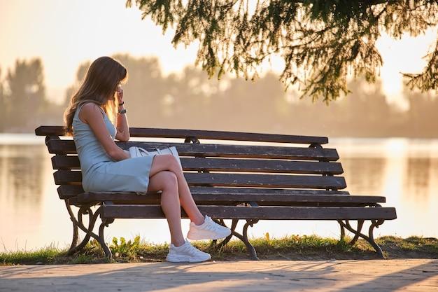 暖かい夏の夜に湖岸のベンチに一人で座っている孤独な悲しい女性。自然の概念の孤独とリラックス。
