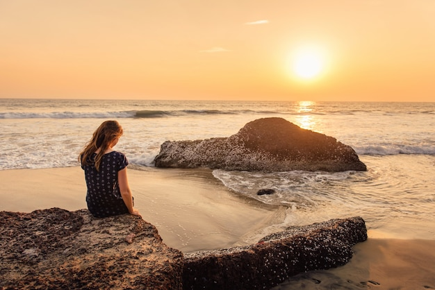 Lonely and sad woman sitting on the rocks and looking at beautiful sea sunset