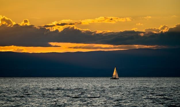 스위스에서 일몰 제네바 호수에 외로운 항해 요트