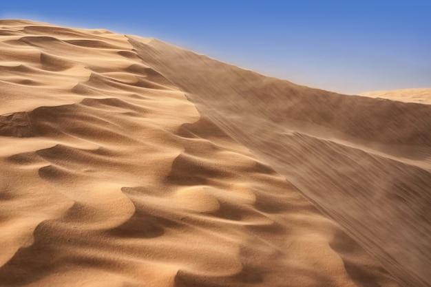 乾燥した砂漠を背景に空の下で強風の中の孤独な砂丘