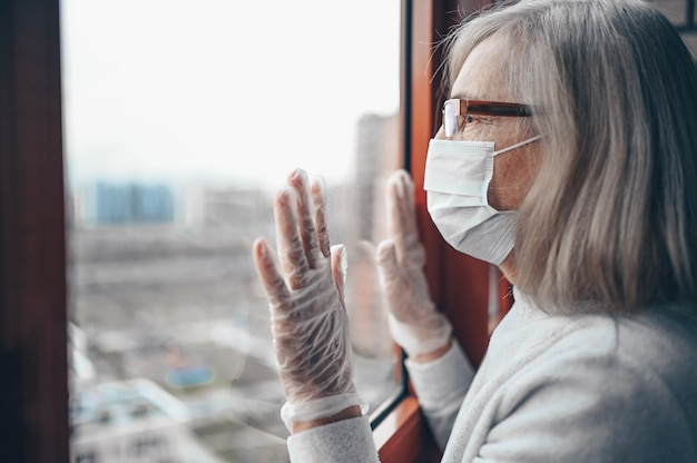 Lonely senior elderly sad woman in medical mask and gloves looking at window stay isolation at home for self quarantine. concept home quarantine, prevention covid-19, coronavirus outbreak situation