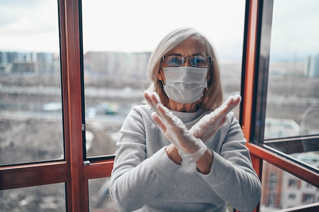 Lonely senior elderly sad woman in medical mask and gloves showing stop sign stay isolation at home for self quarantine. concept home quarantine, prevention covid-19, coronavirus outbreak situation