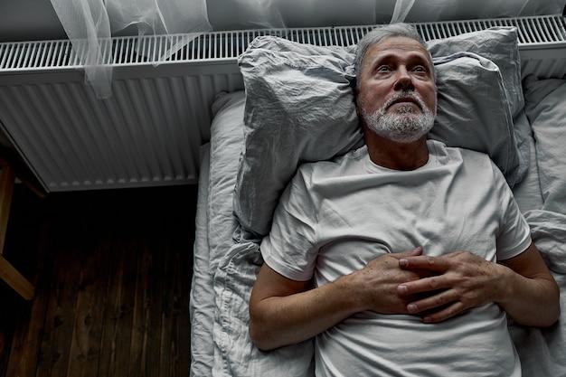 Одинокий старший лежал на кровати в больнице, концепция госпитализации. страдает болезнью одиночества