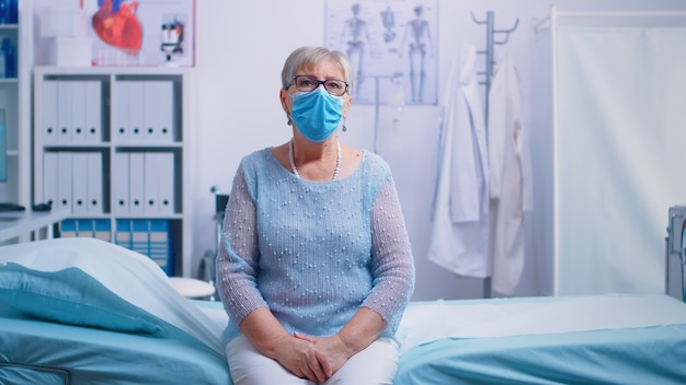 Lonely senior woman in hospital bed wearing a protective mask, waiting for coronavirus result. global health crisis, medical system during pandemic, sick elderly patient in private hospital or clinic