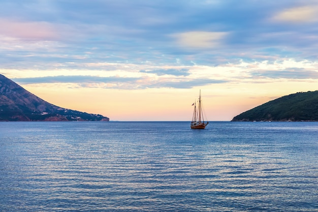 Lonely ship in the harbour of budva, montenegro, sunset view.