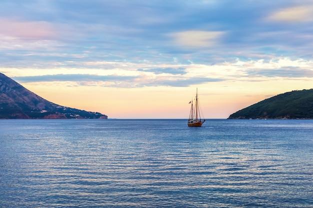 モンテネグロのブドヴァ港に沈む夕日を望む孤独な船。