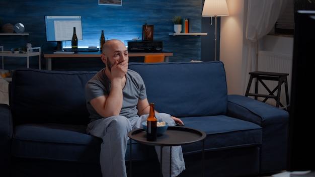 Одинокий шокированный изумленный мужчина смотрит фильм по телевизору ночью и ест попкорн, пьёт пиво, сосредоточенный на ...