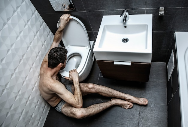 Lonely sick young man hold hands on toilet. he sit in rest room. guy naked. he is going to vomit. illnes and weak.