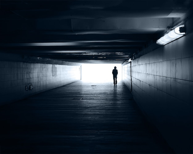 Lonely silhouette in a subway tunnel against the light