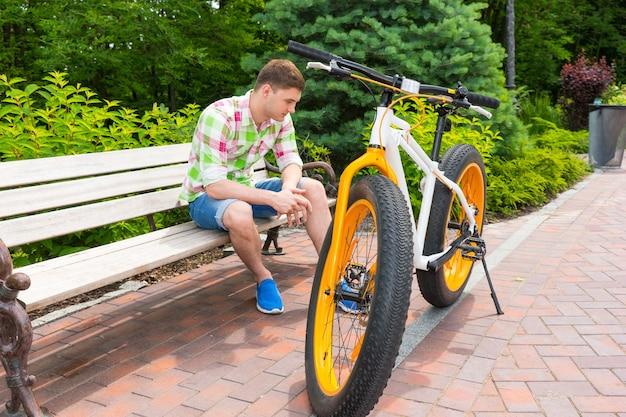 아름다운 녹색 공원의 벽돌 보도에 뚱뚱한 타이어가 주차된 자전거 근처 벤치에 앉아 슬픈 표정으로 반바지를 입은 외로운 독신 남자