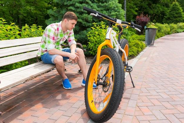 아름다운 녹색 공원의 벽돌 보도에 뚱뚱한 타이어가 주차된 자전거 근처 벤치에 앉아 슬픈 표정을 한 외로운 독신 남자