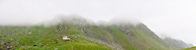 Lonely small house in rocky foggy mountains.