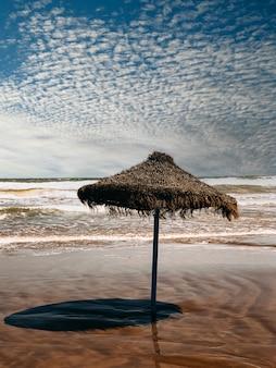 Lonely straw umbrella on seashore