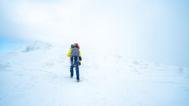 Одинокий туристический поход зимой на вершину горы, покрытой снегом