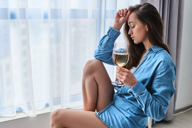 Lonely unhappy drinking woman with closed eyes and white wine glass suffering from alcoholism sits alone at home near window during difficulty life problems and depression