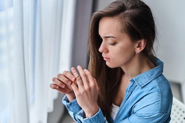 Одинокая несчастная грустная разведенная женщина снимает кольцо с пальца и сидит одна дома у окна во время трудностей, проблем жизни и кризиса в отношениях. разрушить брак и покончить с семьей