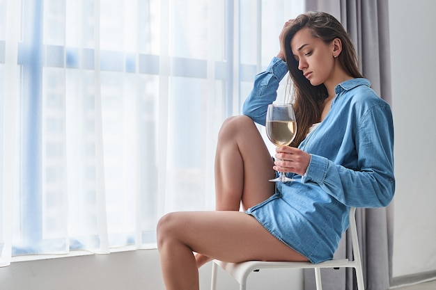 Lonely unhappy sad drinking woman suffering from alcoholism holds in hands wine glass and sits alone at home near window during difficulty life problems and depression