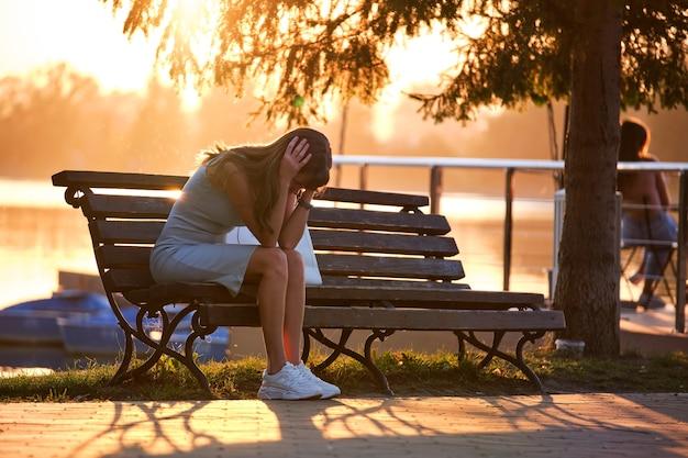 따뜻한 여름 저녁에 공원 벤치에 혼자 앉아 있는 외로운 불행한 젊은 여성. 고독과 자연 개념에서 휴식.