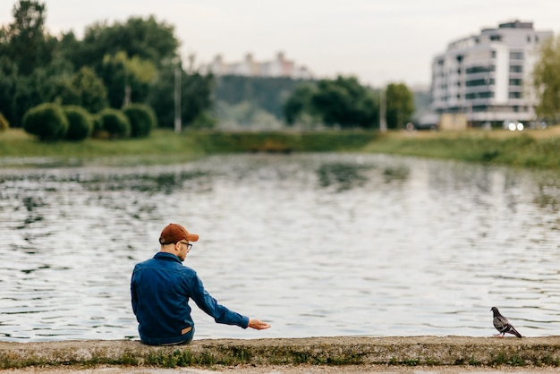 Lonely unrecognizable adult man sitting on edge of embankment in front of lake and calling for dove looking at him