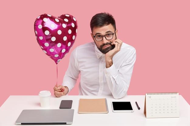 Одинокий небритый мужчина держит подбородок, выражает недовольство, держит валентинку, носит белую рубашку, невежественный вид, сидит на рабочем месте с гаджетами