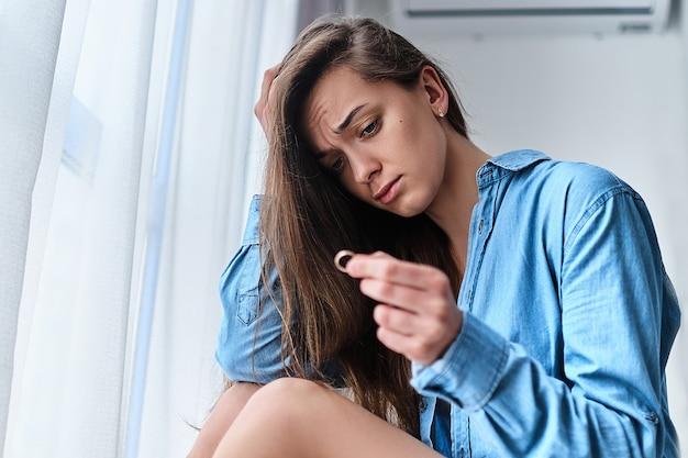悲しそうな目をした孤独な動揺の離婚女性は金の指輪を手に持ち、人生の困難な問題や人間関係の危機の最中に家の窓際で一人で座っています。結婚を壊す
