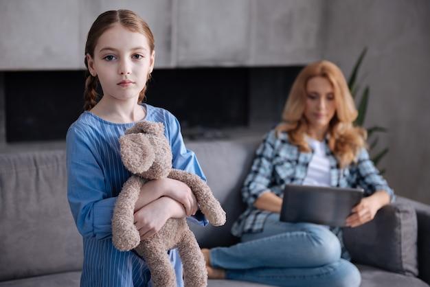 孤独な動揺した憂鬱な子供が家で親の世話を待っていて、母親がタブレットで作業している間、ふわふわのおもちゃを抱きしめています