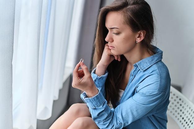 孤独な動揺の悲しい思慮深い離婚女性は金の指輪を手に保持し、人生の問題と関係の危機の間に家に一人で座っています。結婚と離婚を分割する