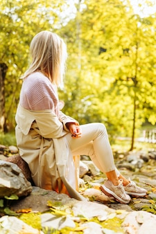 Lonely upset woman wearing cozy warm knitted sweater and coat sit in park at autumn sunny day